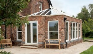Large red brick orangery with white uPVC windows