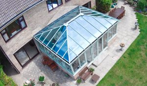 Sage green Edwardian uPVC conservatory with a glass roof