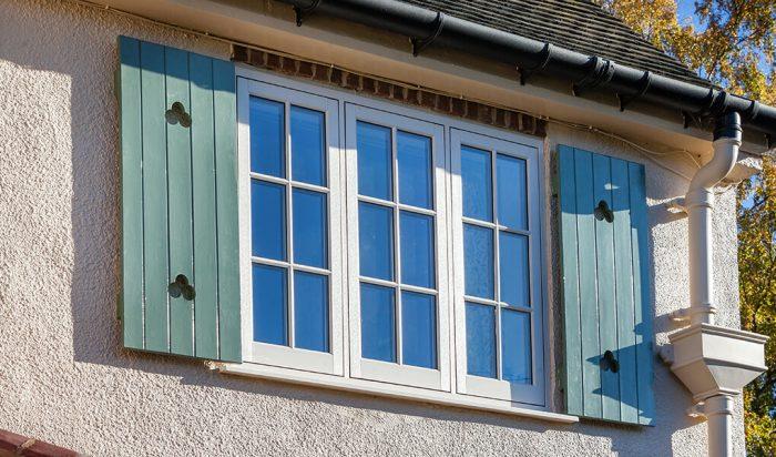 White uPVC flush sash windows with green shutters